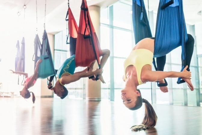Eine Gruppe Frauen macht Aerial Yoga