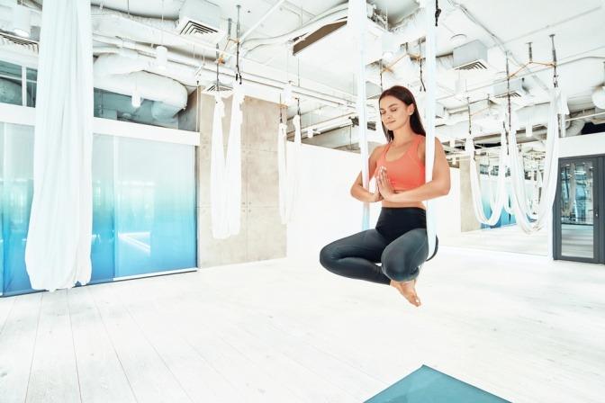 Eine Frau macht beim Aerial Yoga eine Übung