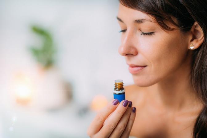 Frau riecht an einem ätherischen Öl