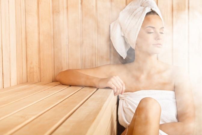 Eine Frau genießt den Duft von ätherischem Öl in der Sauna