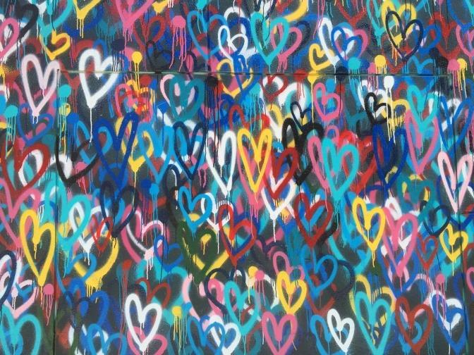 Eine Wand, auf die per Graffiti hunderte kleiner bunter Herzen gesprayt und gemalt wurden.