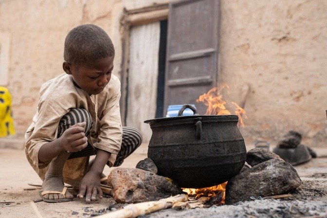 Ein Kind in Afrika sitzt vor einem Kochkessel am Boden