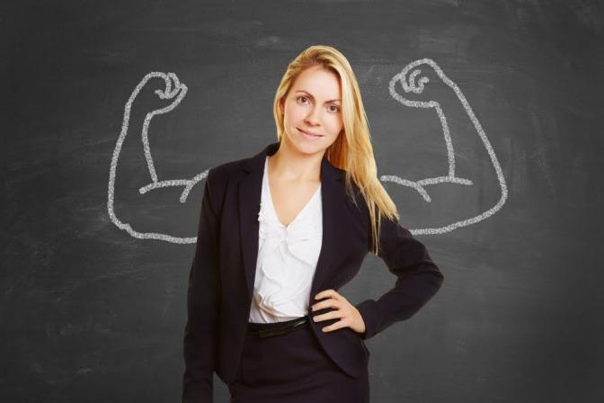 Eine junge Frau im Businessoutfit posiert vor einer Schiefertafel, auf der zwei starke Arme aufgezeichnet sind.
