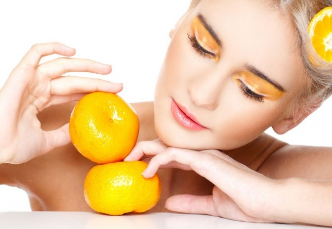Eine Frau spielt mit Zitrusfrüchten, die Fruchtsäuren enthalten