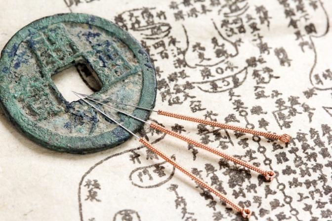 Akupunkturnadeln liegen auf einem Amulett