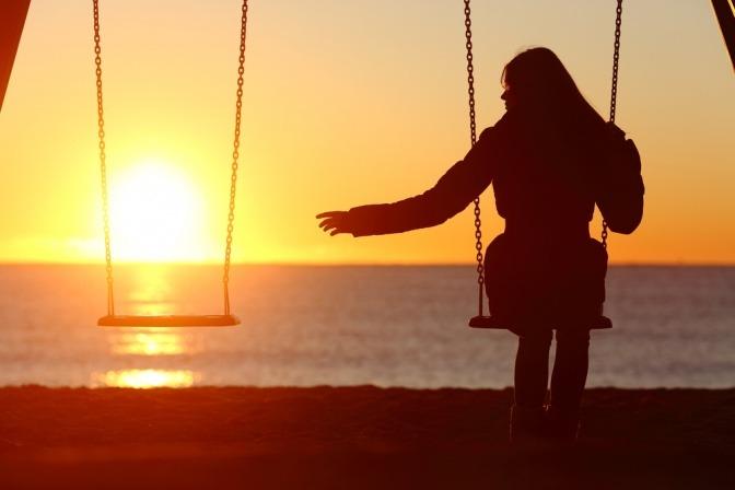 Eine Frau sitzt alleine auf einer Zweierschaukel am Strand.