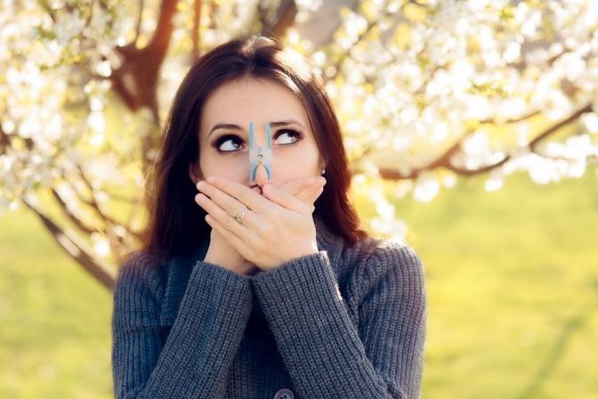 Frau vor blühendem Baum mit Wäscheklammer auf der Nase