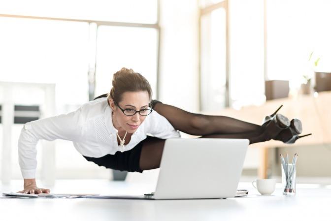Lächelnde Geschäftsfrau, die Yoga im Büro macht.