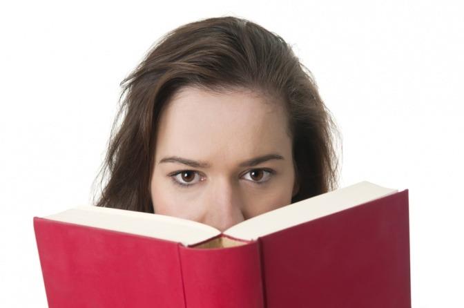 Eine Frau liest angestrengt ein Buch.