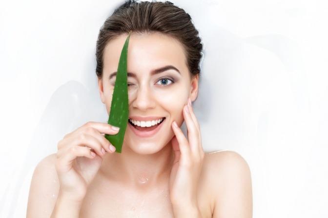 Eine Frau hält ein Aloe Vera Blatt vor ihre Haut