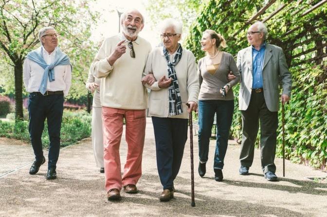 Mehrere Paare in unterschiedlichen, aber eher hohen Altersgruppen machen einen Spaziergang durch einen Park.
