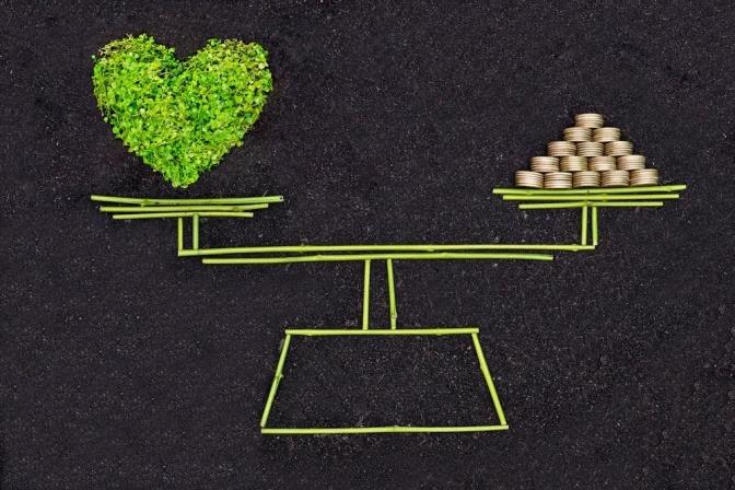 Eine Waage im Gleichgewicht: in der einen Waagschale befinden sich Bilder von Herzen, in der anderen Münzen.