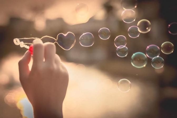 Jemand pustet Seifenblasen in Herzchenform in die Luft.