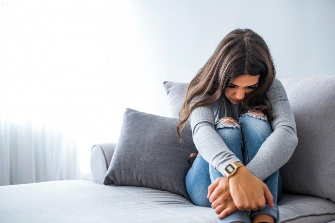 Eine Frau mit Angst vor Menschen sitzt zusammengekauert auf der Couch