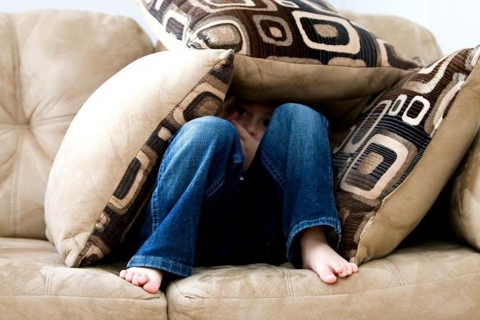 Ein Kind hat Angst vor Veränderungen und versteckt sich unter Kissen
