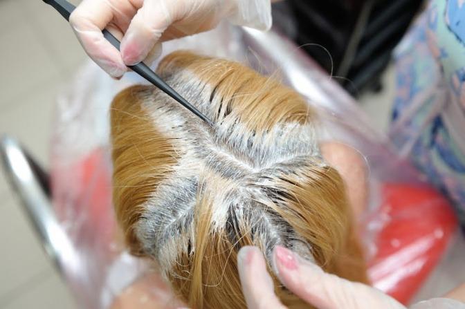 Mit einem Pinsel wird ein Haaransatz nachgefärbt