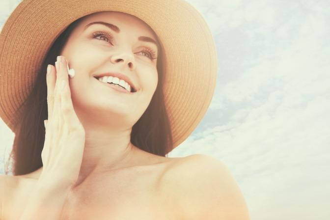 Eine Frau mit Sonnenhut gibt Antipollutioncreme ins Gesicht