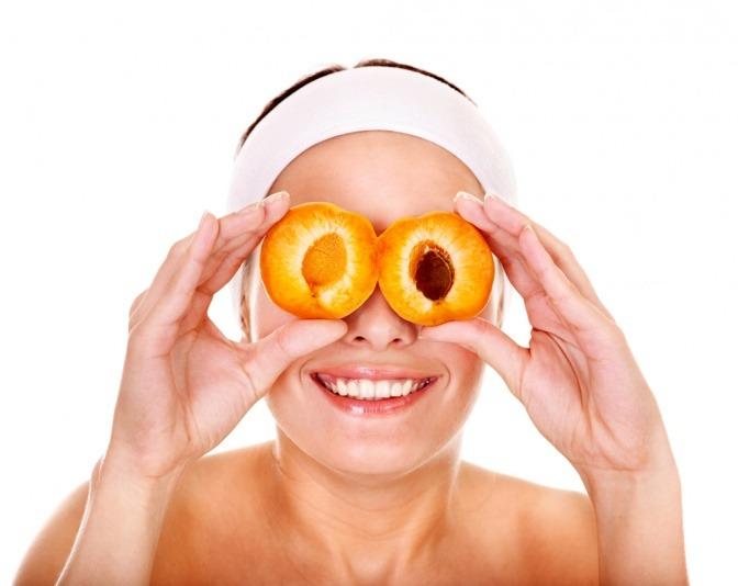Eine Frau hält Aprikosen auf Ihre Haut