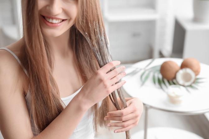 Frau massiert Kokosöl in ihre Haare ein