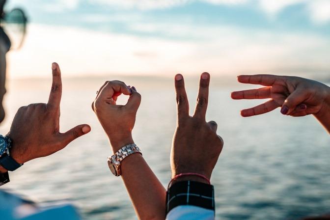 Die Hände eines Mannes und einer Frau formen jeweils die Buchstaben für das Wort LOVE.