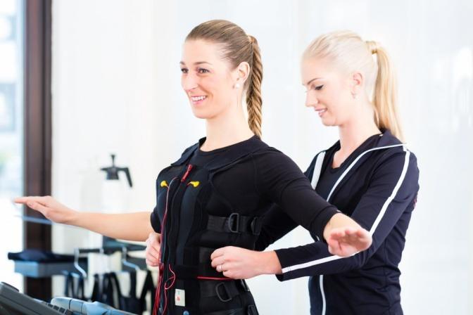 Trainerin richtet den EMS-Anzug