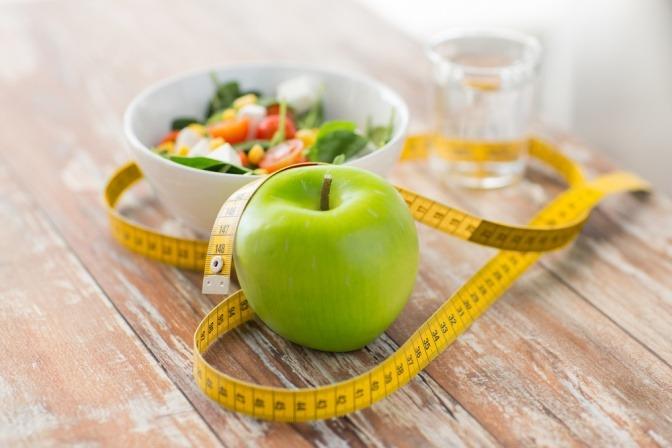 Ein Maßband liegt um einen Apfel und eine Schüssel mit Salat
