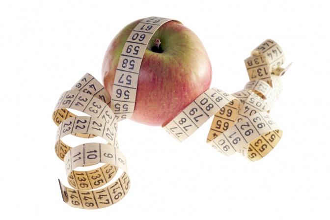 Ein Maßband ist um einen Apfel gelegt