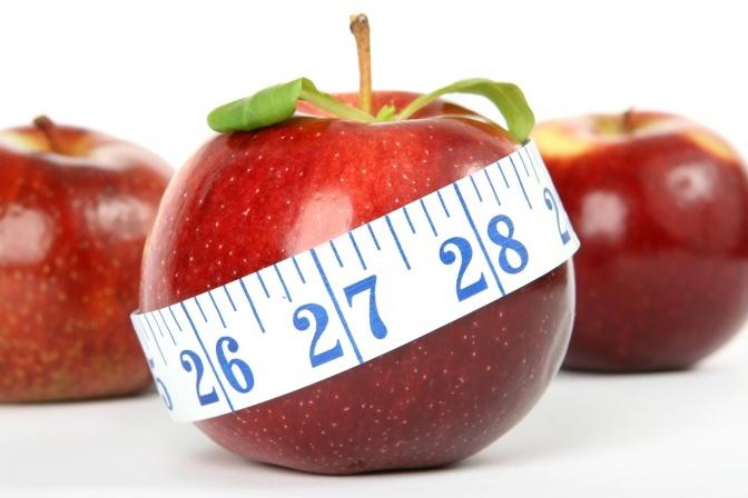 Ein Massband wickelt sich um einen roten Apfel