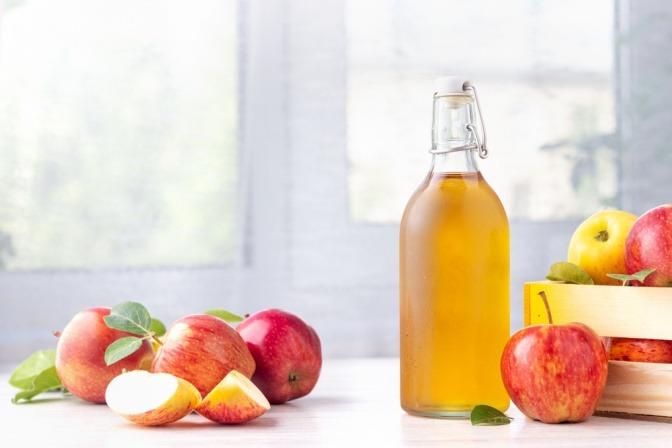 Apfelessigflasche und frische Äpfel.