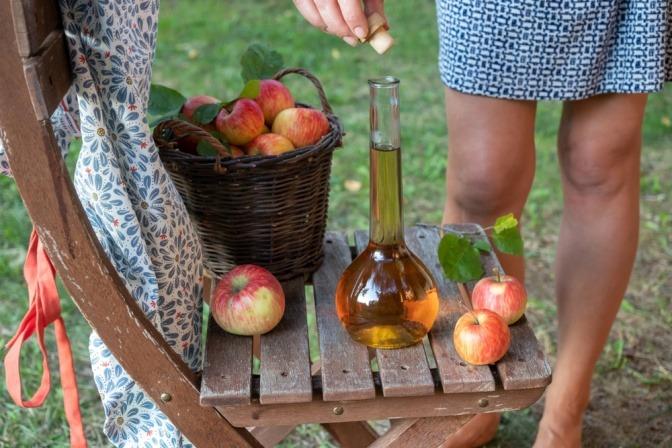 Eine Frau und Apfelessig, um Besenreiser vorzubeugen