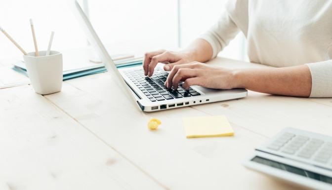 Frau tippt am Laptop