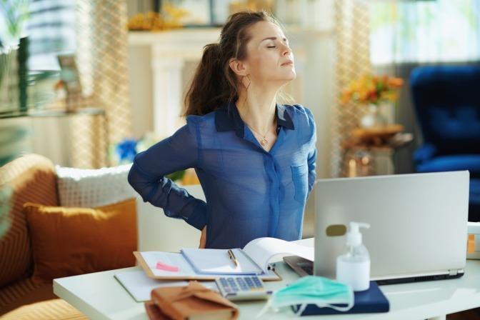 Frau am Arbeitsplatz fasst sich an schmerzenden Rücken.