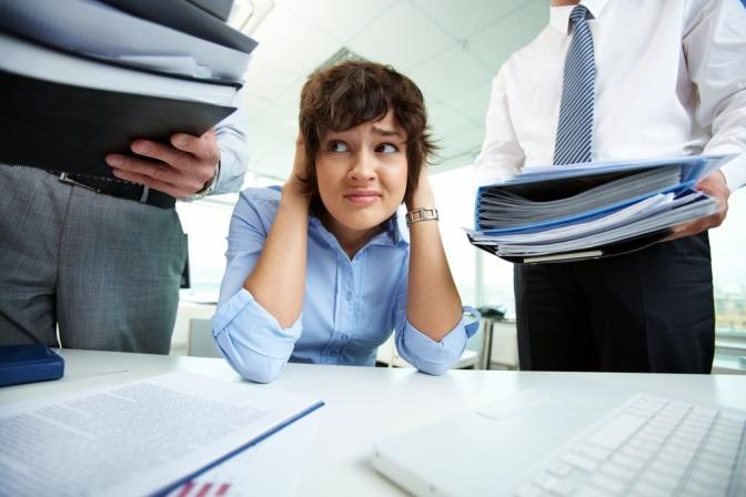 Eine Frau am Schreibtisch wird mit Aufgaben von Kollegen und Vorgesetzten überladen.