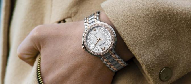 Eine Dame hat eine Armbanduhr aus Metall
