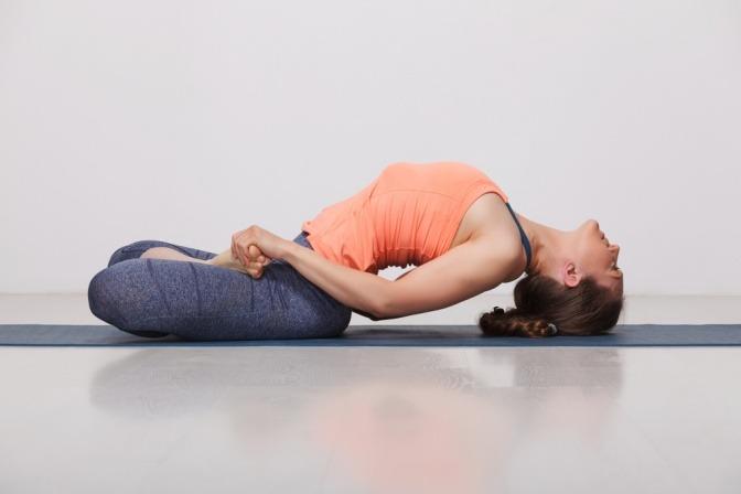 Eine Frau führt eine Asana (Bewegungsübung) aus