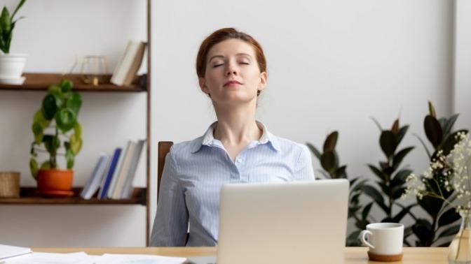 Frau im Büro macht Atemübungen gegen Stress