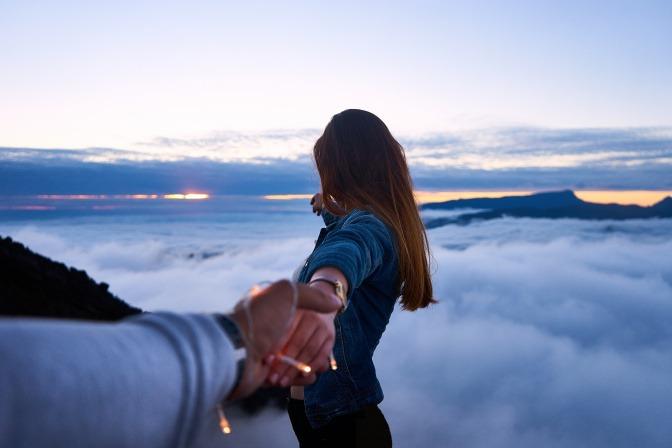 Eine Frau zieht einen Mann an der Hand in Wolkenhöhe