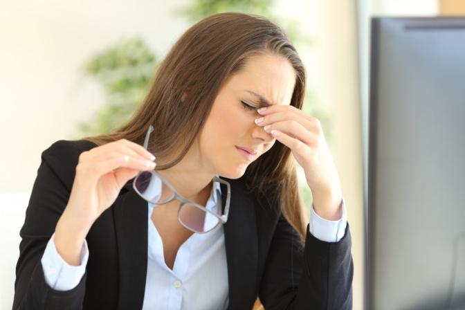 Frau vor Computer mit Schmerzen