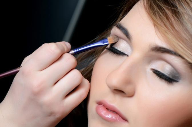 Eine Frau mit einem auffallenden Augen Make-up in Pink-Lilatönen schminkt sich mit einem Pinsel