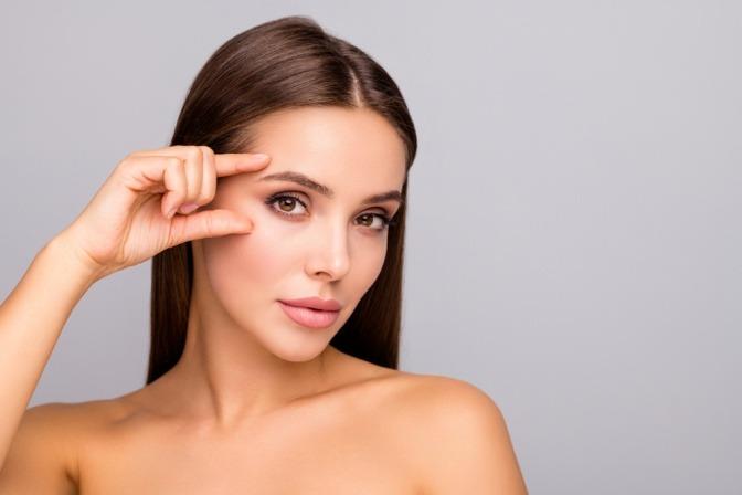 Frau zeigt auf Augenbrauen, die richtig geformt sind