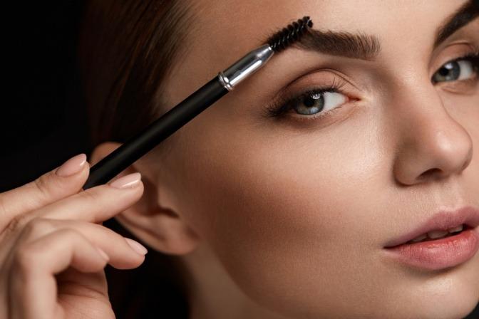 Eine Frau ist beim Augenbrauen schminken mit Bürstchen