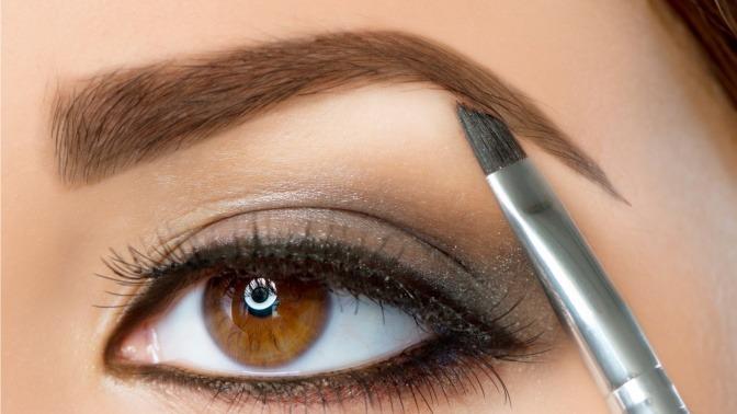Eine Frau schminkt ihre Augenbrauen