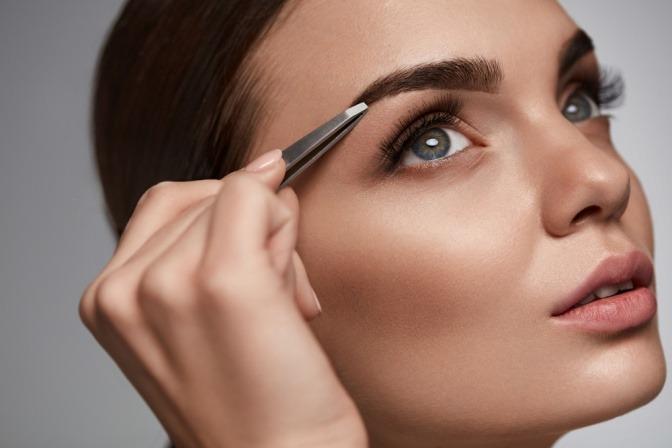 Frau verwendet Augenbrauenstift zum Schminken der Augenbrauen