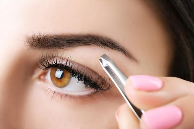 Eine Frau zupft Ihre Augenbrauen