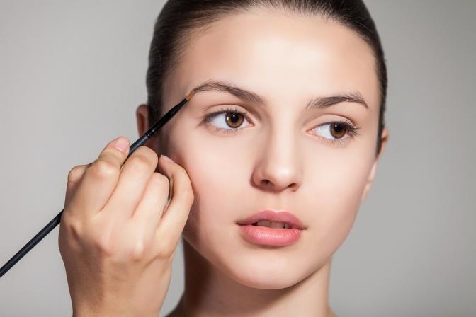 Eine Frau ist beim Augenbrauen Schminken mit einem Pinsel