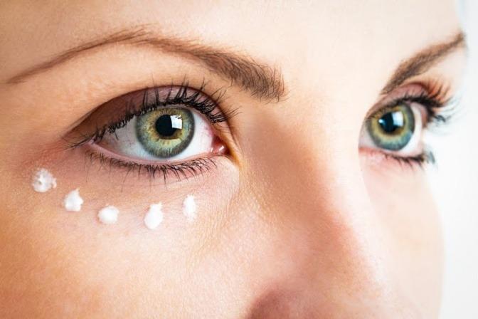 Eine Frau trägt Creme unter dem Auge auf