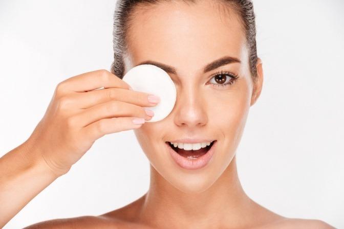 Eine Frau reinigt ihre Augenlider