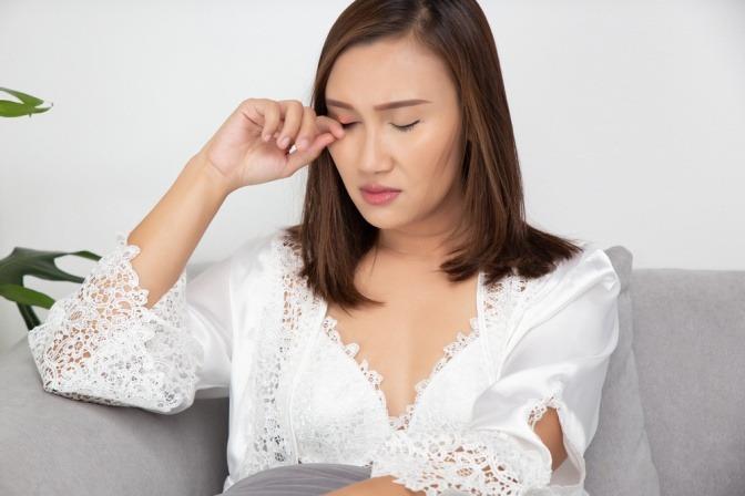 Eine Frau hat ein Augenlidekzem und vergessen vorzubeugen