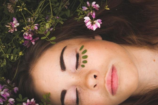 Eine junge Frau deckt ihre Augenringe mit kleinen Blättern ab