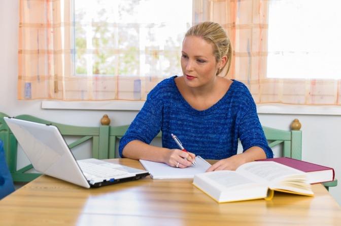 Eine junge Frau lernt für Ihre Mykotherapie Ausbildung, die sie online absolviert.